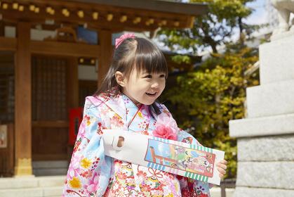 千歳飴を持つ七五三の日本人の女の子