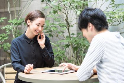 テラスでタブレットPCを使う外国人の男女