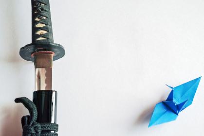 白い紙の上に置いた抜きかけの黒い日本刀と青い折り鶴