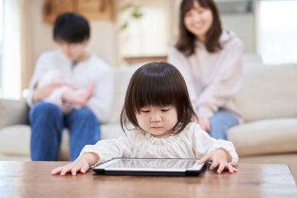 1人でタブレットを見るアジア人の女の子