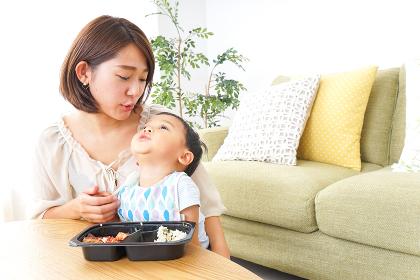 子どもにごはんを食べさせる母親