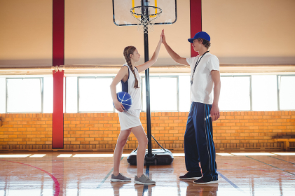 Male coach doing high five with female basketball player