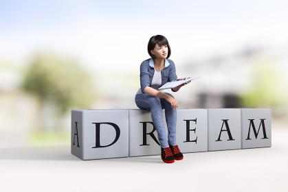 DREAMと書かれた箱に座って本広げた黒地に赤い差し色のスニーカーを履いた女子が斜め上を見上げている