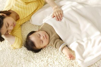 リビングで昼寝をする赤ちゃんと添い寝するお母さん