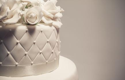 Details of a wedding cake, decoration with white fondant on grey backg