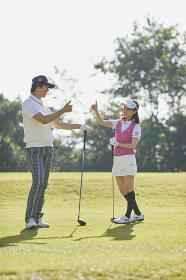 ゴルフ サムズアップをする日本人カップル
