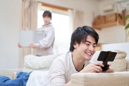 家事をする女性とゲームをするアジア人男性
