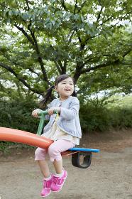 シーソーで遊ぶ日本人の女の子