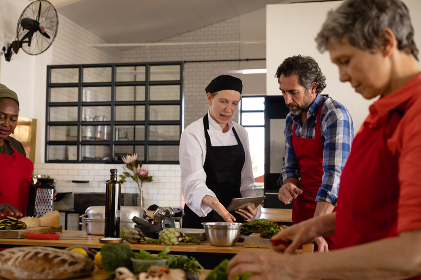 Side view of a multi-ethnic group of Senior adults at a cookery class, the diverse adult students, standing at wooden tables of ingredients preparing food, listening to instructions from a Caucasian female chef wearing chefs whites and a black hat and apron using a tablet computer