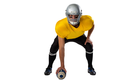 Portrait of American football player wearing helmet bending while holding ball