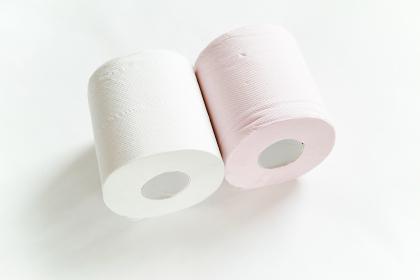白バックの中央に2ロール転がるように置いてある白とピンクの新品のトイレットペーパー