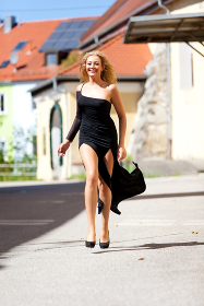 Running blonde woman with black dress