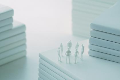 積み重ねた白い本とミニチュアの人間の無機質な世界