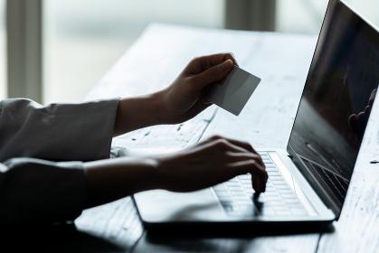 クレジットカードを持ちパソコン作業をする若い女性のシルエット姿