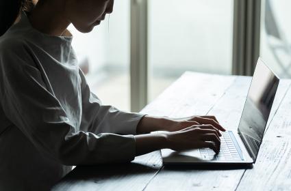 暗い部屋の中でパソコン作業をする若い女性のシルエット姿