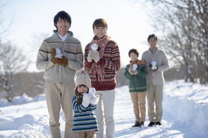 雪だるまを持ち微笑む3世代家族