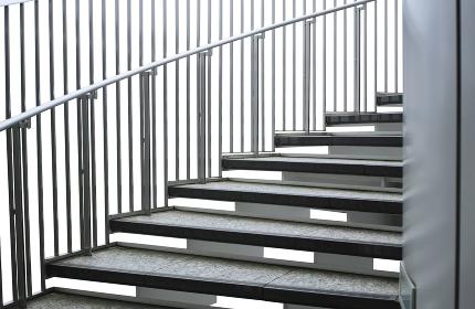 白バックの柵と手すりのある屋外螺旋階段