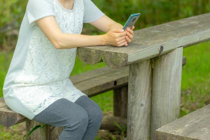 ベンチに座ってスマートフォンを扱う女性