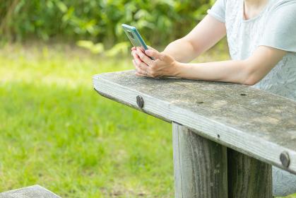 屋外でベンチに座ってスマーフォンを扱う女性