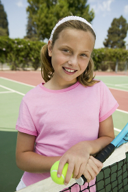 Young girl with tennis racket and ball by net at tennis court portrait