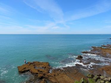 青い海の海岸の岩場で釣りをする人