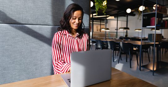 Front view of a mixed race businesswoman working in a modern office, sitting by a desk and using a laptop computer. Social distancing and self isolation in quarantine lockdown