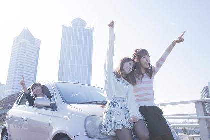 遠くを指差す女性と、車の前で楽しそうに手を上げる友達