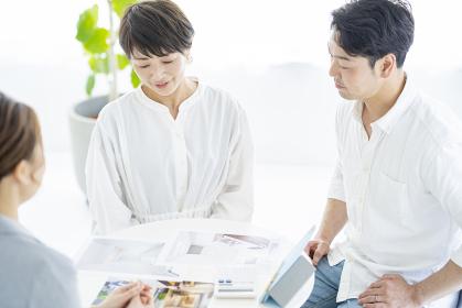スーツ姿の女性から住宅とインテリアの説明を受ける夫婦