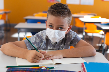 Portrait of caucasian schoolboy wearing face mask sitting at desk in classroom writing in book. childhood and education at elementary school during coronavirus covid 19 pandemic.