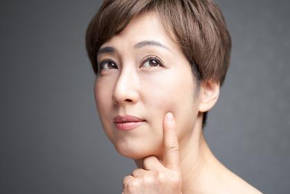肌のハリを確かめる中年の日本人女性
