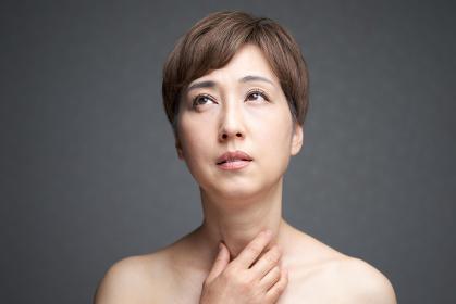 喉に痛みを感じる中年の日本人女性