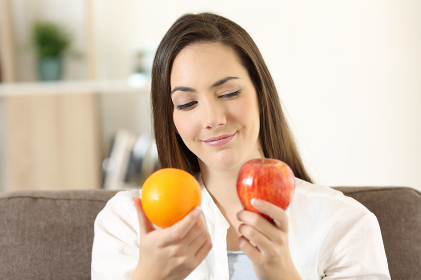 Girl deciding between two fruits