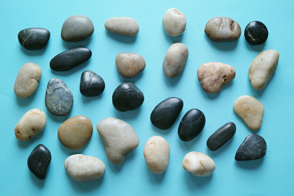 青い紙の背景に置いた複数の小石。平置きの俯瞰撮影。