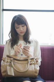 電車でスマートフォンを操作する女性
