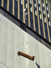 建設中の高層ビルのクレーンで吊り揚げる鉄骨