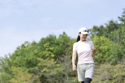 運動中スマートフォンを操作する中年女性