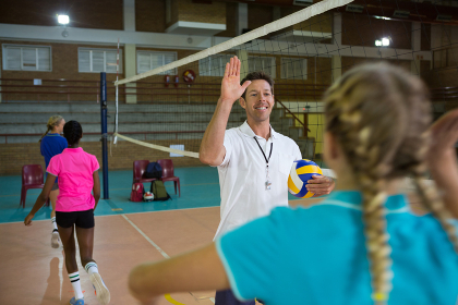 Coach giving high five to female player in volleyball court