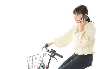 自転車でスマホを使う若い女性