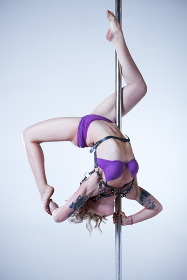 Young sexy pole dance woman in pink lingerie. Tattoo on body.
