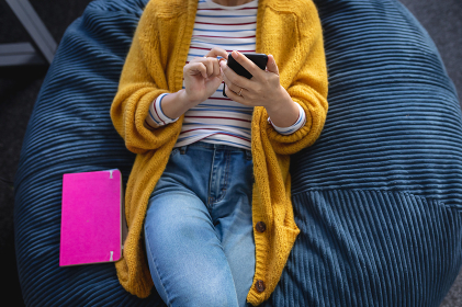 Midsection of businesswoman chilling in office relaxing space lying in beanbag using a smartphone. independent creative design business.