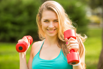 Sports girl exercise with dumbbells in the park