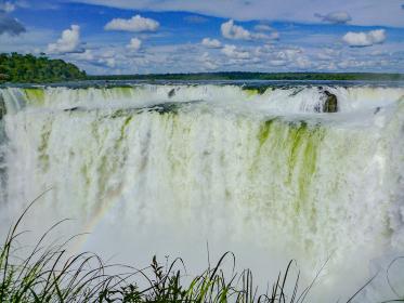 アルゼンチン・ブラジル国境エリアのイグアスの滝にて虹のかかった悪魔の喉笛と青空