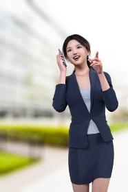 大きなビルの前を携帯電話で話しながら目的地に歩くスーツの女性社員