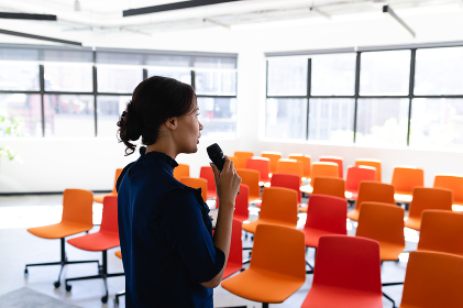 Side view of a mixed race businesswoman wearing smart clothes, standing in an empty modern meeting room, training herself before the conference.