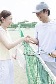 テニスの試合後に握手をする男女