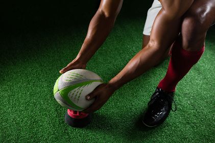High angle view of sportsman keeping rugby ball on tee