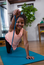 Smiling girl performing exercise on exercise mat