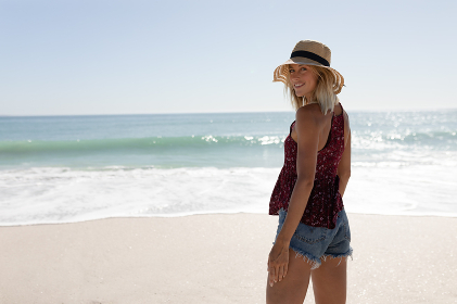 Blonde Caucasian woman wearing a straw hat and denim shorts, enjoying free time walking by the sea on an idyllic sunny beach, turning and smiling to camera. Relaxing tropical beach holiday