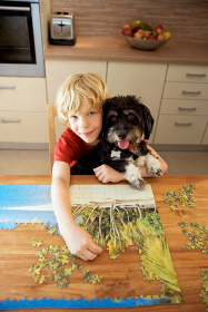 A boy holding a dog while doing a puzzle