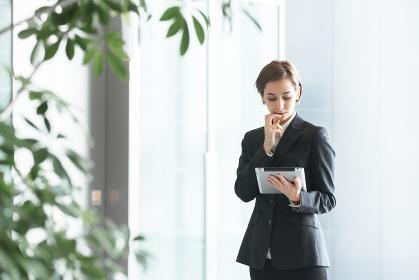 タブレットPCを持つ女性(ビジネスイメージ)